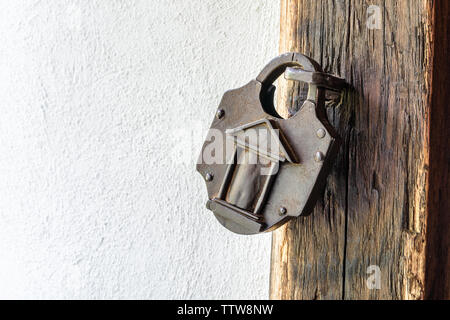 Interesting old padlock on a wooden medieval door. Vintage padlock. - Stock Photo