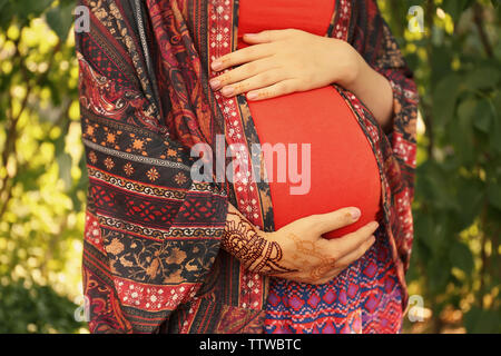 Young pregnant woman with henna tattoo on hand in park - Stock Photo