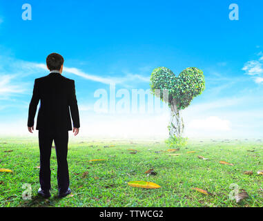 Businessman stands on a large tree lawn in the shape of only one heart. - Stock Photo
