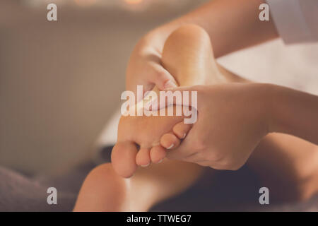 Young woman having feet massage in beauty salon, close up view - Stock Photo