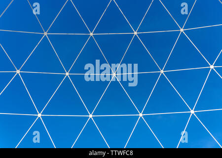 Metal white lattice in the form of geometric shapes on a background of blue sky, close up - Stock Photo