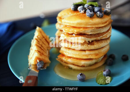 Stack of delicious pancakes with blueberries and mint on plate, closeup - Stock Photo