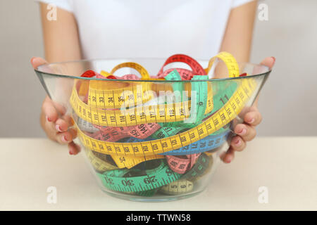 Woman holding bowl with measuring tape on white  background - Stock Photo