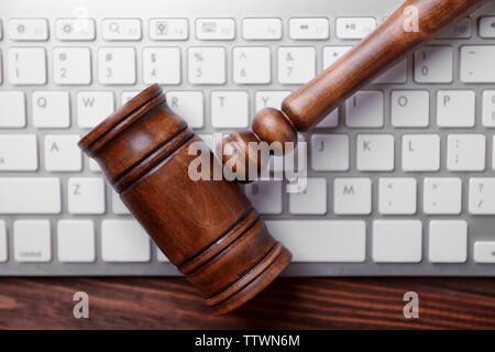 Wooden gavel and keyboard on desk - Stock Photo