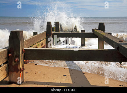A view of the sea breaking against a wooden breakwater on the Norfolk coast at Cart Gap, Happisburgh, Norfolk, England, United Kingdom, Europe. - Stock Photo