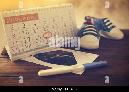 Calendar with mark, ultrasound picture of baby and children shoes on table - Stock Photo
