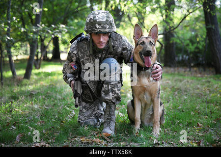Soldier with german shepherd dog in forest - Stock Photo