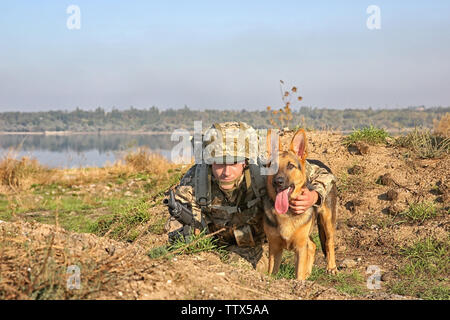 Soldier with german shepherd dog at military firing range - Stock Photo