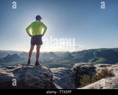 Silhouette of athlete runner on sunset background copy space. Sportsman jogging in evening catching the sun. Man with sportive figure practices sport - Stock Photo