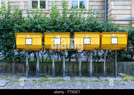 Four yellow post boxes for posting letters on a sidewalk in Charlottenburg-Berlin. - Stock Photo