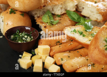 Tasty bakery products with garlic and herbs, close up view - Stock Photo