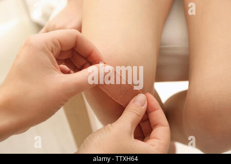 Female hands applying plaster on girl's knee, closeup - Stock Photo