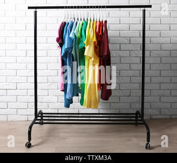 Colorful t-shirts on hangers against brick wall Stock Photo