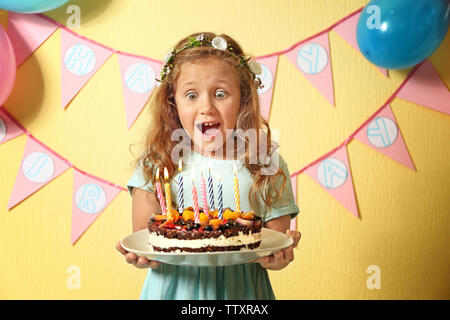 Funny little girl holding plate with birthday cake at home - Stock Photo