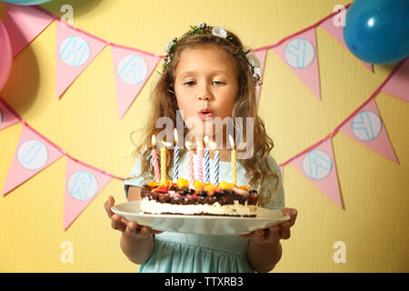 Cute little girl blowing out candles on birthday cake at home - Stock Photo