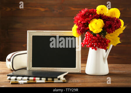 Vintage brown frame with flowers in vase on brown wooden background - Stock Photo