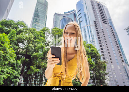 Woman Tourist using navigation app on the mobile phone. Navigation map on a smartphone in a big city - Stock Photo