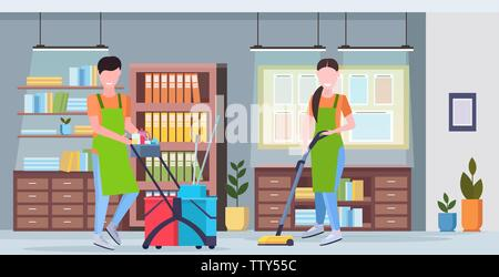 man pushing trolley cart with cleaning supplies woman using vacuum cleaner couple cleaners in uniform working together modern co-working center office - Stock Photo