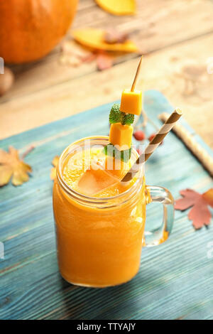Jar with pumpkin smoothie on wooden background - Stock Photo