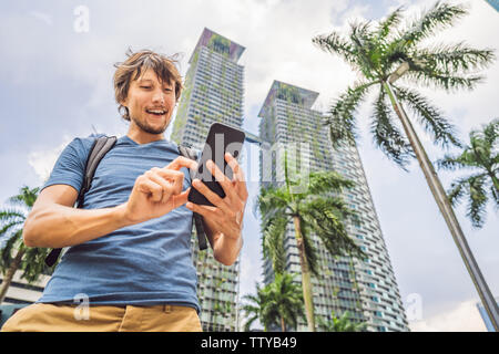 Man Tourist using navigation app on the mobile phone. Navigation map on a smartphone in a big city - Stock Photo