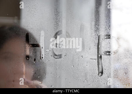 Word HELP written by young woman on steamy window, view from outside - Stock Photo