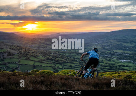 A man rides an ebike from the summit of The Blorenge in the Brecon Beacons, near Abergavenny, Monmouthshire, Wales. Mountain biking Wales. - Stock Photo
