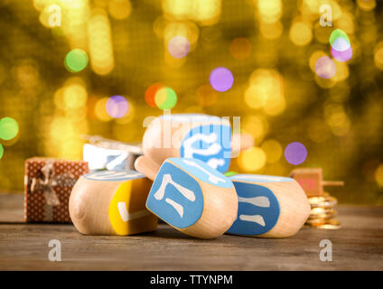 Dreidels for Hanukkah on wooden table against defocused lights - Stock Photo