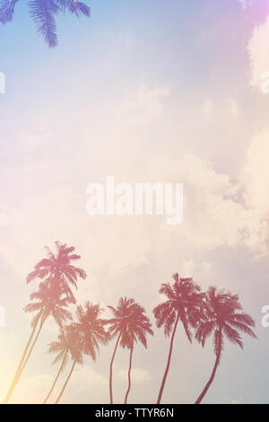 Coconut palm trees on ocean beach. Tropical coast palms vintage stylized with film light flare leaks. - Stock Photo
