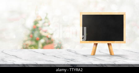 merry christmas banner,Mock up blackboard on white marble table with blur christmas tree and snow fall background with bokeh light. banner for display - Stock Photo