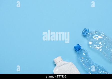 Single use crushed plastic bottles on blue background with copy space. Plastic pollution. Recycle reuse template.