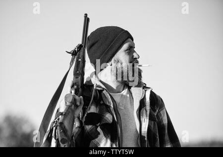 Man brutal bearded guy gamekeeper blue sky background. Hunter with rifle gun close up. Guy bearded hunter spend leisure hunting and smoking. Brutality and masculinity. Hunting masculine hobby concept. - Stock Photo