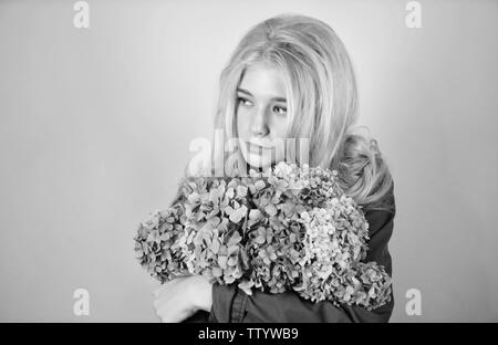 Pure beauty. Tenderness of young skin. Springtime bloom. Simple beauty. Girl cute blonde hug hydrangea flowers bouquet. Natural beauty concept. Skin care and beauty treatment. Gentle delicate flower. - Stock Photo