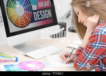 Beautiful young designer working in office - Stock Photo