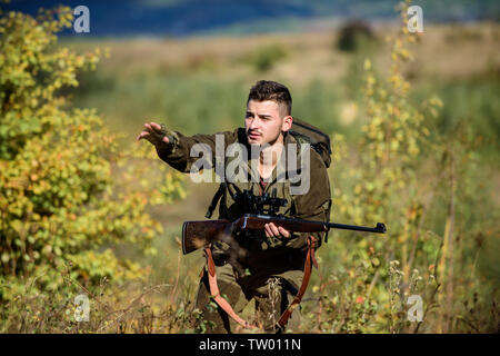 Hunter hold rifle. Man wear camouflage clothes nature background. Hunting permit. Hunting equipment for professionals. Hunting is brutal masculine hobby. Bearded serious hunter spend leisure hunting. - Stock Photo