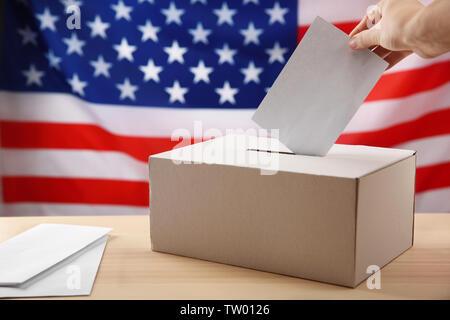 Hand inserting envelope in ballot box on USA national flag background - Stock Photo