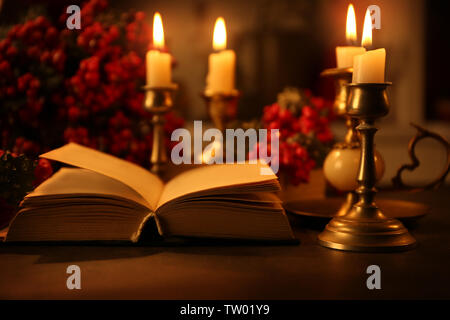 Open Bible and burning candles on table - Stock Photo