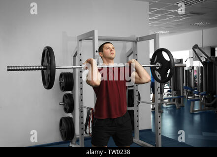 Young handsome man with barbell training in gym - Stock Photo