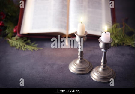 Burning candles and blurred open Bible on grey table - Stock Photo