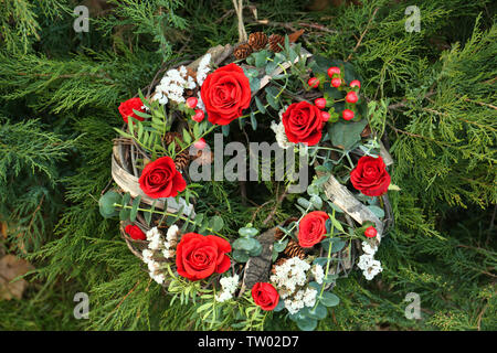 Floral wreath with beautiful flowers on thuja branches background - Stock Photo