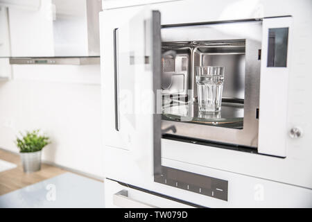Built-in microwave oven  in the kitchen with a cup of pure water. - Stock Photo