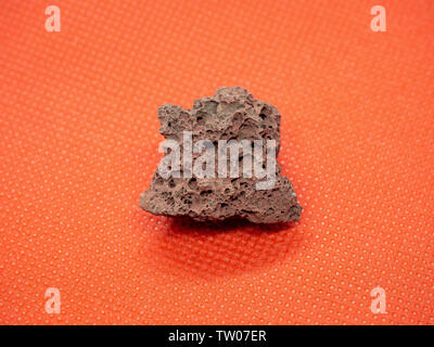 Geological specimen of natural red Pumice (pumicite, volcanic rock) on red background - Stock Photo