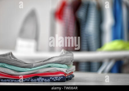 Clean clothes on table at home - Stock Photo