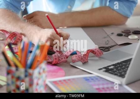 Closeup of fashion designer drawing at office - Stock Photo