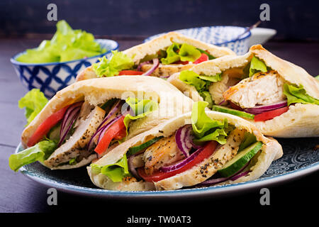 Pita stuffed with chicken, tomato and lettuce on wooden background. Middle Eastern cuisine. - Stock Photo