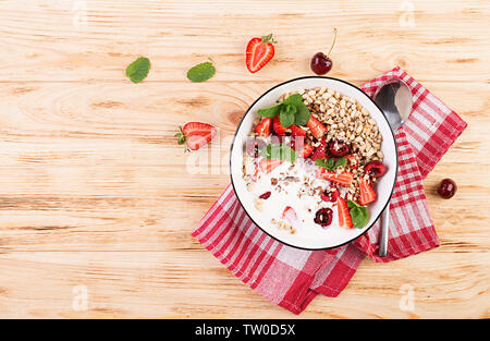 Healthy breakfast - granola, strawberries, cherry, nuts and yogurt in a bowl on a wooden table. Vegetarian concept food. Top view - Stock Photo