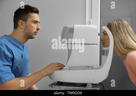 Ophthalmologist measuring intraocular pressure of young woman in clinic - Stock Photo