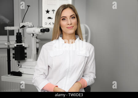 Beautiful young ophthalmologist in clinic - Stock Photo