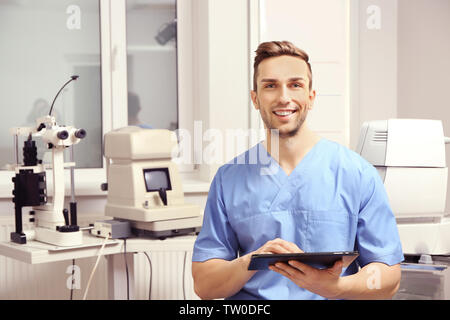 Handsome young ophthalmologist with tablet computer in clinic - Stock Photo