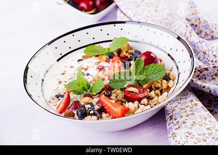Healthy breakfast - granola, strawberries, cherry, honeysuckle berry, nuts and yogurt in a bowl. Vegetarian concept food. - Stock Photo