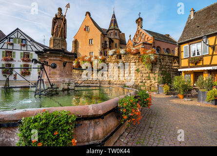 picturesque place in the old village Eguisheim, Alsace, France, scenic square with castle Château de Saint-Léon-Pfalz and well - Stock Photo